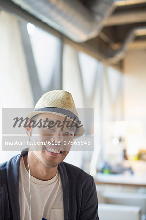 Portrait of smiling casual businessman in fedora Stock Photo - Premium Royalty-Free, Image code: 6113-07565943