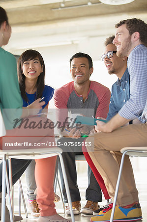 Creative business people meeting in circle of chairs Stock Photo - Premium Royalty-Free, Image code: 6113-07565953