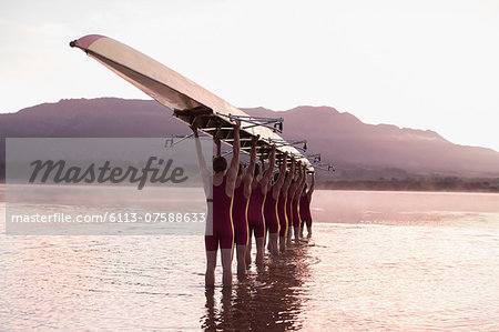 Rowing team carrying row boat overhead in still lake Stock Photo - Premium Royalty-Free, Image code: 6113-07588633