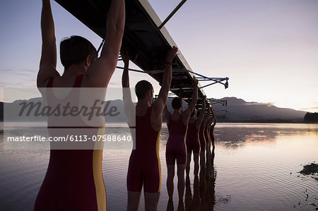 Rowing team carrying boat overhead into lake Stock Photo - Premium Royalty-Free, Image code: 6113-07588640