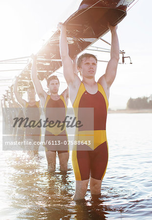 Rowing team carrying boat overhead on lake Stock Photo - Premium Royalty-Free, Image code: 6113-07588643