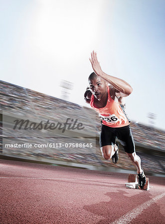 Sprinter taking off from starting block Stock Photo - Premium Royalty-Free, Image code: 6113-07588645