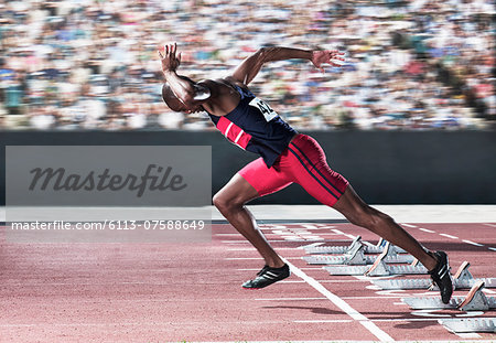Sprinter taking off from starting block on track Stock Photo - Premium Royalty-Free, Image code: 6113-07588649