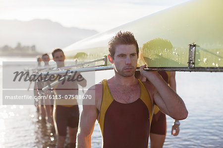 Rowing team carrying scull out of lake Stock Photo - Premium Royalty-Free, Image code: 6113-07588670