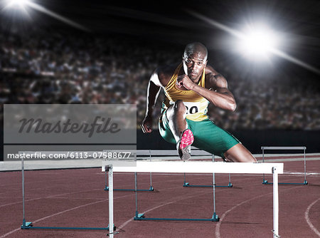 Runner clearing hurdle on track Stock Photo - Premium Royalty-Free, Image code: 6113-07588677