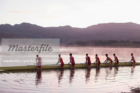 Rowing crew placing scull in lake at dawn Stock Photo - Premium Royalty-Free, Image code: 6113-07588680