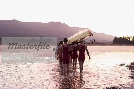 Rowing team carrying scull into lake Stock Photo - Premium Royalty-Free, Image code: 6113-07588691