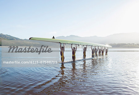 Rowing team holding scull overhead in lake Stock Photo - Premium Royalty-Free, Image code: 6113-07588705