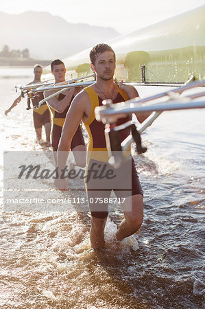 Rowing team carrying scull in lake Stock Photo - Premium Royalty-Free, Image code: 6113-07588717