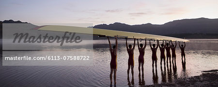 Rowing crew holding scull overhead in lake Stock Photo - Premium Royalty-Free, Image code: 6113-07588722