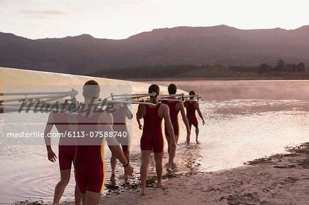 Rowing team carrying scull into lake at dawn Stock Photo - Premium Royalty-Free, Image code: 6113-07588740