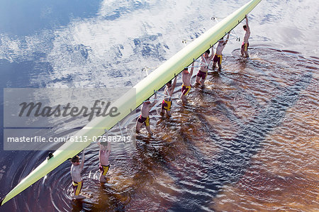 Rowing crew carrying scull overhead in lake Stock Photo - Premium Royalty-Free, Image code: 6113-07588749