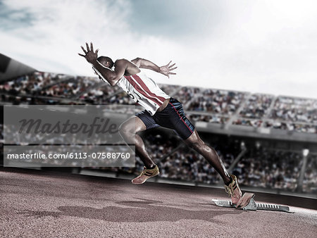 Runner taking off from starting block on track Stock Photo - Premium Royalty-Free, Image code: 6113-07588760