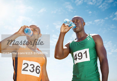 Runners drinking water on track Stock Photo - Premium Royalty-Free, Image code: 6113-07588776