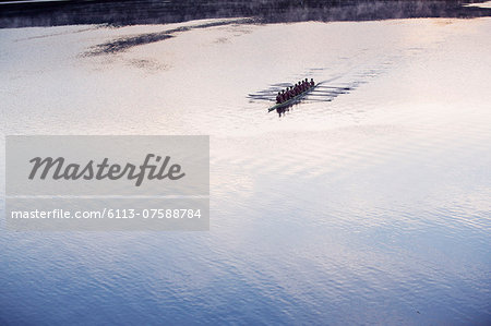 Rowing crew rowing scull on lake in distance Stock Photo - Premium Royalty-Free, Image code: 6113-07588784