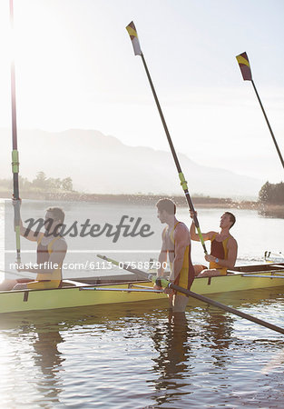 Rowing team lifting oars in lake Stock Photo - Premium Royalty-Free, Image code: 6113-07588790
