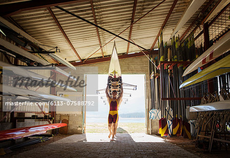 Rowing team carrying scull into shed Stock Photo - Premium Royalty-Free, Image code: 6113-07588792