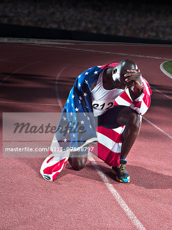 Track and field athlete wrapped in American flag on track Stock Photo - Premium Royalty-Free, Image code: 6113-07588797