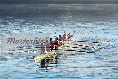 Rowing team celebrating in scull on lake Stock Photo - Premium Royalty-Free, Image code: 6113-07588802