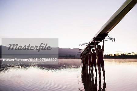 Rowing team entering lake at dawn with scull overhead Stock Photo - Premium Royalty-Free, Image code: 6113-07588807