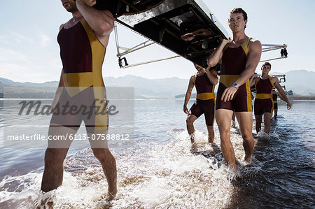 Rowing team carrying scull out of lake Stock Photo - Premium Royalty-Free, Image code: 6113-07588812