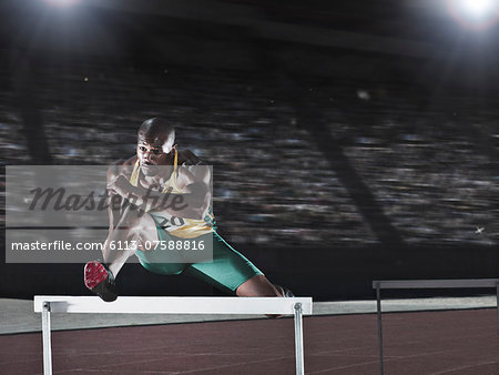 Runner jumping hurdle on track Stock Photo - Premium Royalty-Free, Image code: 6113-07588816