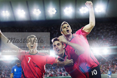Soccer players celebrating on field Stock Photo - Premium Royalty-Free, Image code: 6113-07588840