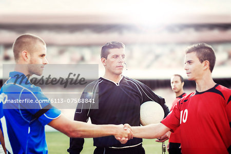Soccer players shaking hands on field Stock Photo - Premium Royalty-Free, Image code: 6113-07588841
