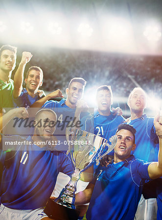 Soccer team celebrating with trophy in stadium Stock Photo - Premium Royalty-Free, Image code: 6113-07588843