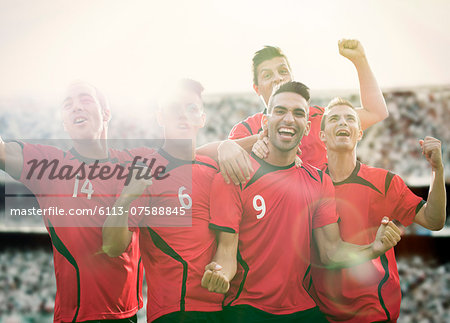 Soccer team celebrating on field Stock Photo - Premium Royalty-Free, Image code: 6113-07588845