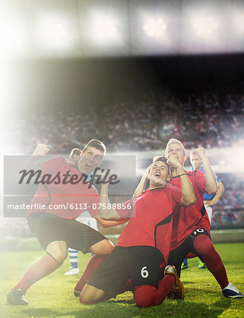 Soccer team celebrating on field Stock Photo - Premium Royalty-Free, Image code: 6113-07588856