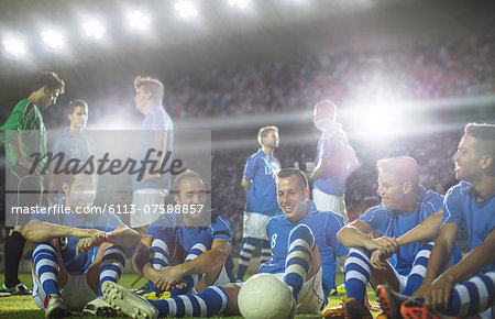 Soccer team relaxing on field Stock Photo - Premium Royalty-Free, Image code: 6113-07588857