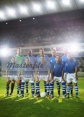 Soccer team posing on field Stock Photo - Premium Royalty-Free, Image code: 6113-07588859