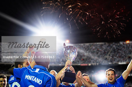 Soccer team celebrating with trophy on field Stock Photo - Premium Royalty-Free, Image code: 6113-07588863
