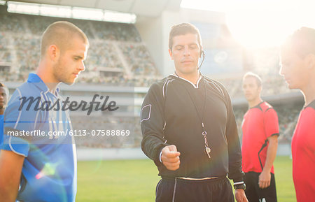 Referee tossing coin during soccer game Stock Photo - Premium Royalty-Free, Image code: 6113-07588869