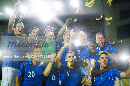 Soccer team celebrating with trophy on field Stock Photo - Premium Royalty-Free, Image code: 6113-07588877