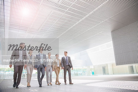 Business people walking in modern courtyard Stock Photo - Premium Royalty-Free, Image code: 6113-07588900