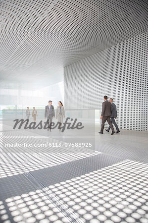 Business people walking outside modern building Stock Photo - Premium Royalty-Free, Image code: 6113-07588925