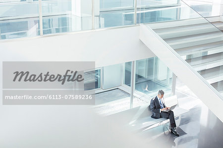 Businessman using laptop in modern office Stock Photo - Premium Royalty-Free, Image code: 6113-07589236