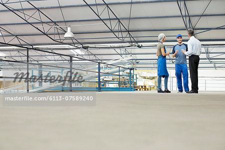 Supervisor and workers talking in food processing plant Stock Photo - Premium Royalty-Free, Image code: 6113-07589240