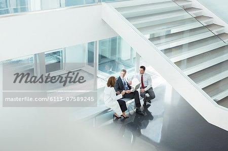 Doctor and administrators talking in hospital lobby Stock Photo - Premium Royalty-Free, Image code: 6113-07589245