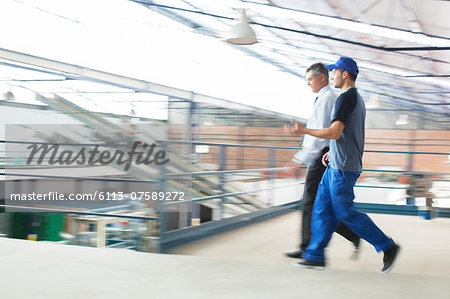 Supervisor and worker walking in food processing plant Stock Photo - Premium Royalty-Free, Image code: 6113-07589272