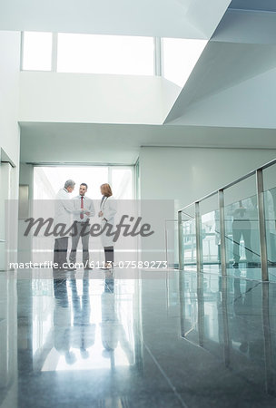 Doctors and administrators talking in hospital corridor Stock Photo - Premium Royalty-Free, Image code: 6113-07589273