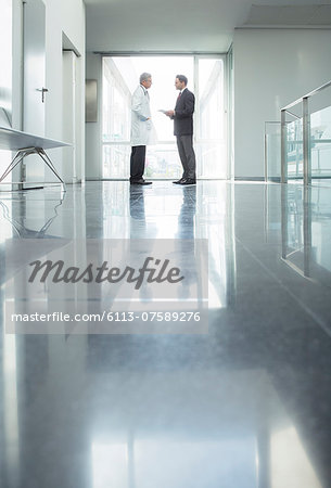 Doctor and administrator talking in hospital corridor Stock Photo - Premium Royalty-Free, Image code: 6113-07589276