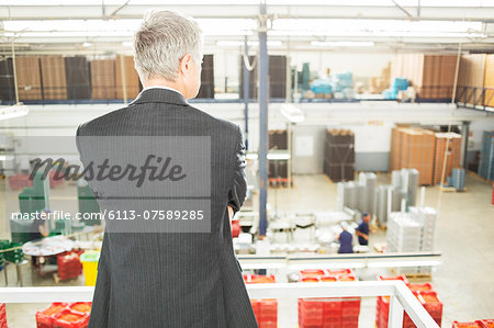 Supervisor watching workers in food processing plant Stock Photo - Premium Royalty-Free, Image code: 6113-07589285