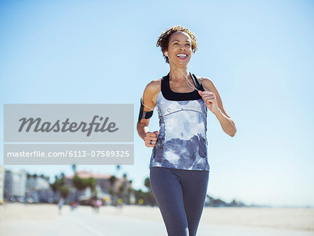 Woman running on beach Stock Photo - Premium Royalty-Free, Image code: 6113-07589325