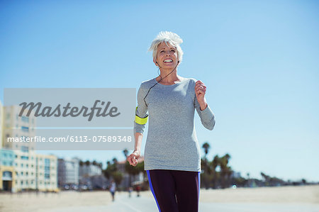 Senior woman power walking on beach Stock Photo - Premium Royalty-Free, Image code: 6113-07589348