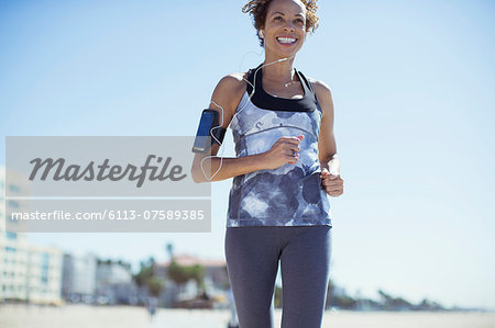 Woman jogging on beach Stock Photo - Premium Royalty-Free, Image code: 6113-07589385