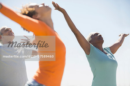Seniors practicing yoga outdoors