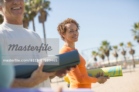 Portrait of smiling woman with yoga mat at beach